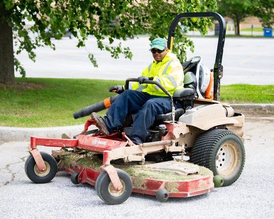 A lawn mowing service worker cuts the grass around the West Manchester Town Center, May 8, 2019.