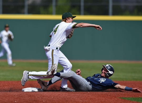Manogue's Jack Weise throws to first for the double play at Damonte's Nate Guidara sliding into second base during Wednesday's game at Bishop Manogue High School on May 8, 2019.
