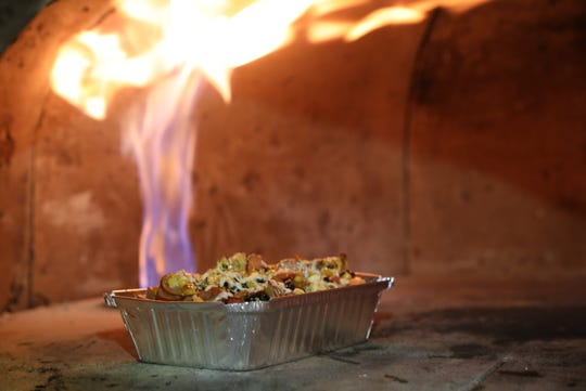 An order of Dantes Peak pasta is finished in the wood-fired oven.