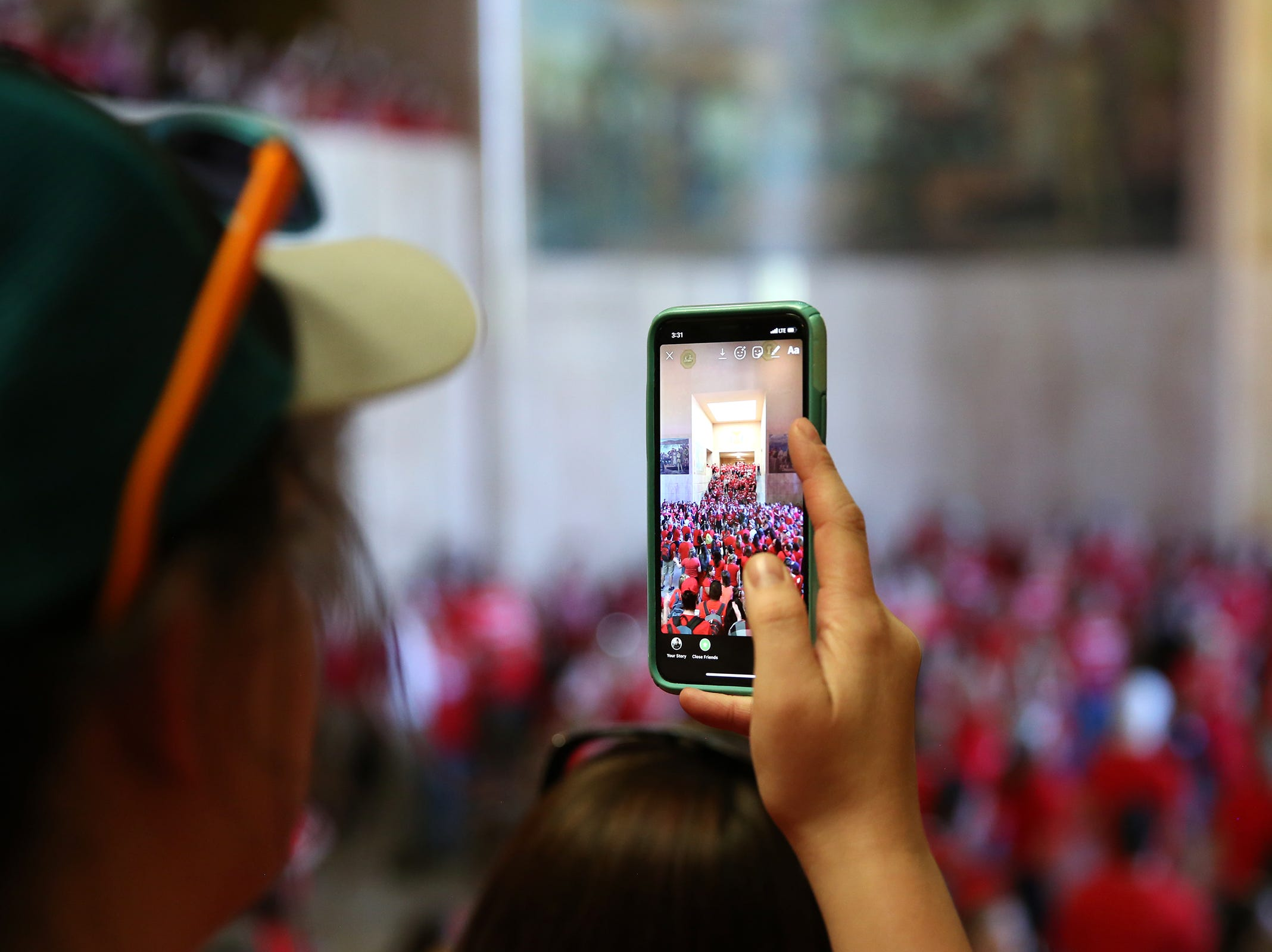 Michelle Dickson, a North Salem High School teacher, takes a snapchat as thousands of teachers and education activists fill the rotunda to demand funding at the Oregon State Capitol in Salem on May 8, 2019.