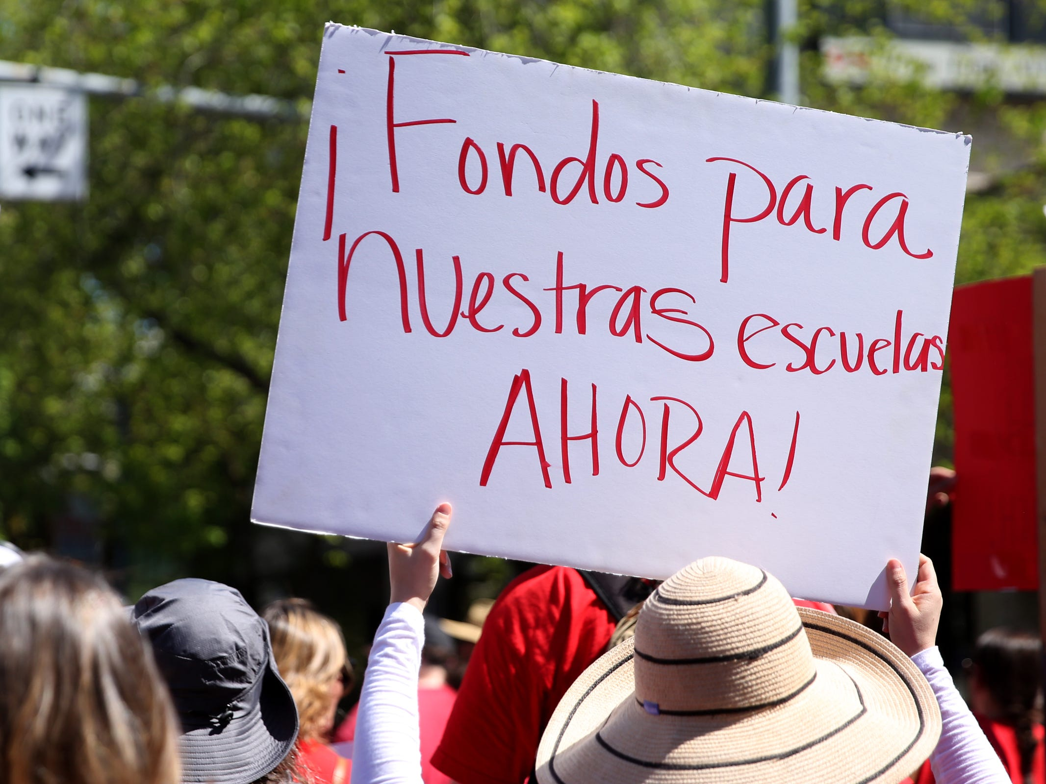 "A woman carries a sign reading ""Funds for our schools now"" in Spanish as thousands of teachers and education activists march from Riverfront Park to the Oregon State Capitol for a day of action in Salem on May 8, 2019. Schools across Oregon closed early or were closed for the day as teachers walked out to demand more school funding to address large class sizes, low graduation rates and other concerns."
