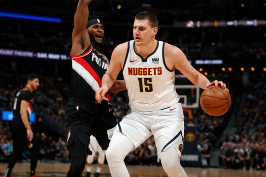 Denver Nuggets center Nikola Jokic, right, drives to the rim for a basket as Portland Trail Blazers forward Maurice Harkless defends in the first half of Game 5 of an NBA basketball second-round playoff series, Tuesday, May 7, 2019, in Denver.