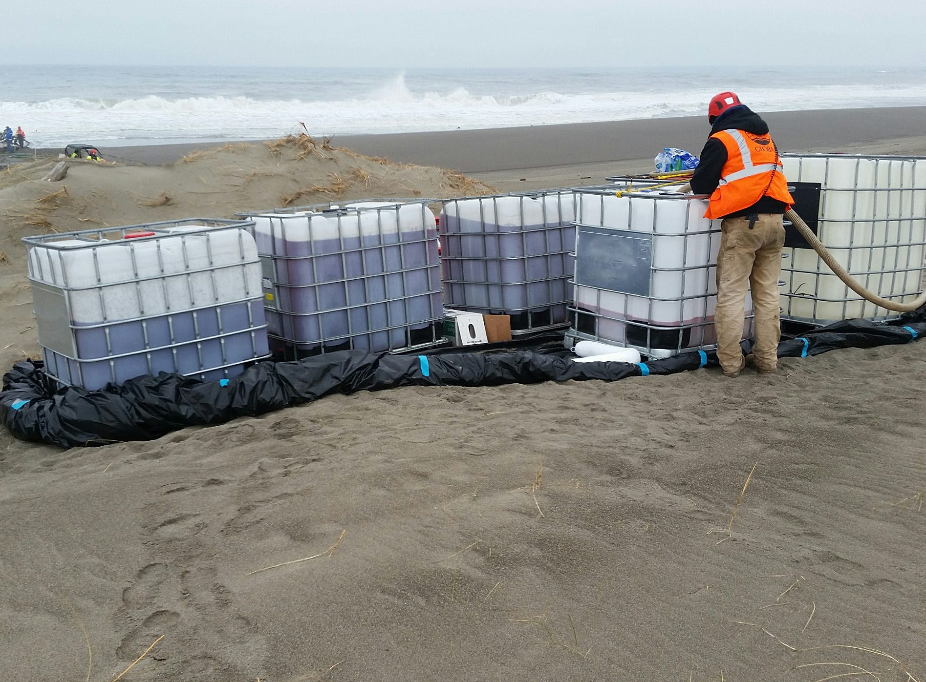 A contracted salvage worker recovers diesel fuel from the wreck of the 64-foot commercial fishing vessel Ann Kathleen on a beach near Bandon, May 4, 2019.