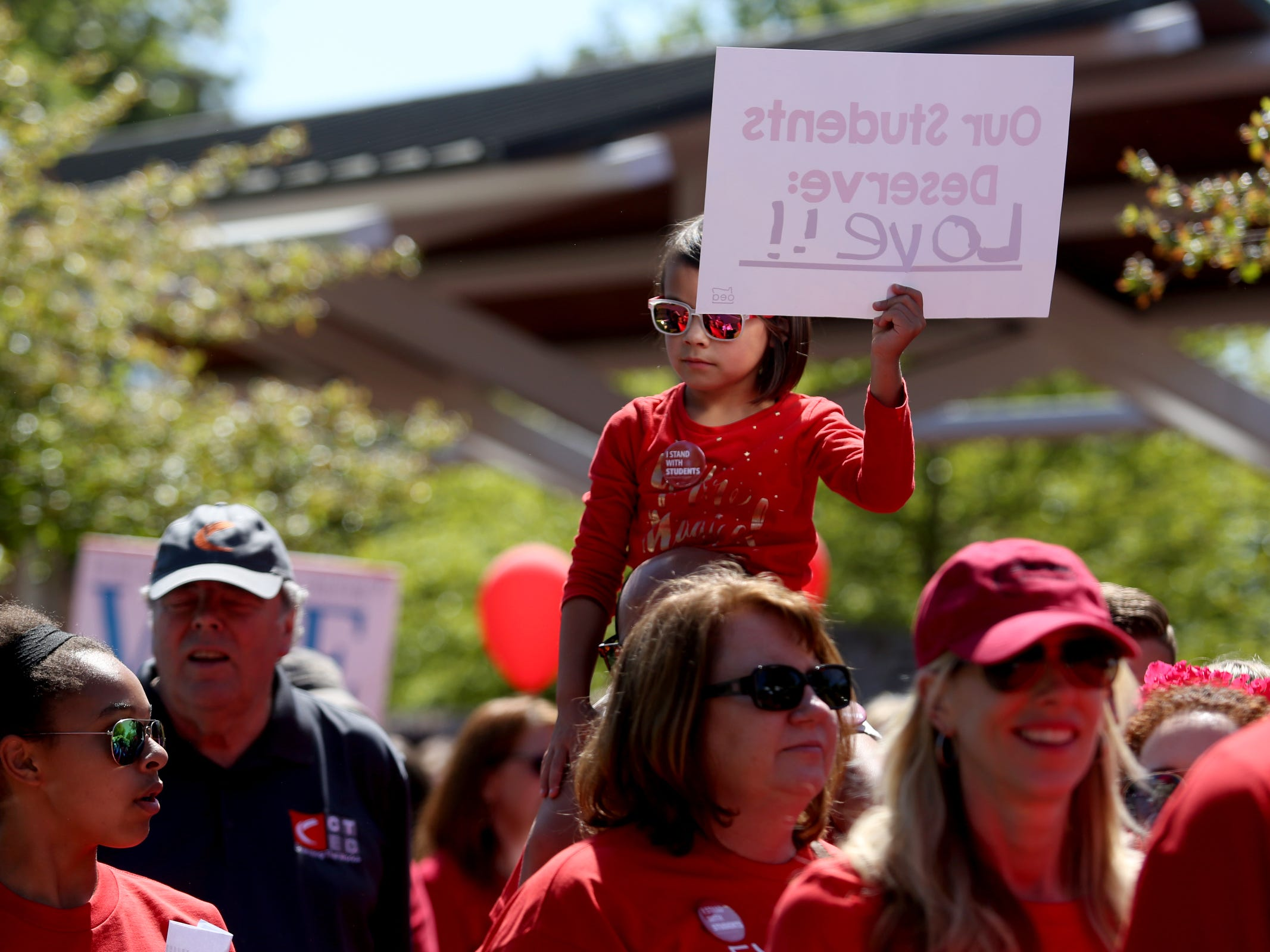 Marley Sonis, 7, of Salem, gets a view from above as thousands of teachers and education activists march from Riverfront Park to the Oregon State Capitol for a day of action in Salem on May 8, 2019. Schools across Oregon closed early or were closed for the day as teachers walked out to demand more school funding to address large class sizes, low graduation rates and other concerns.