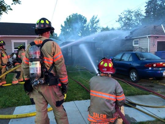 Fire crews douse a fire on Breyman Street NE Tuesday evening.
