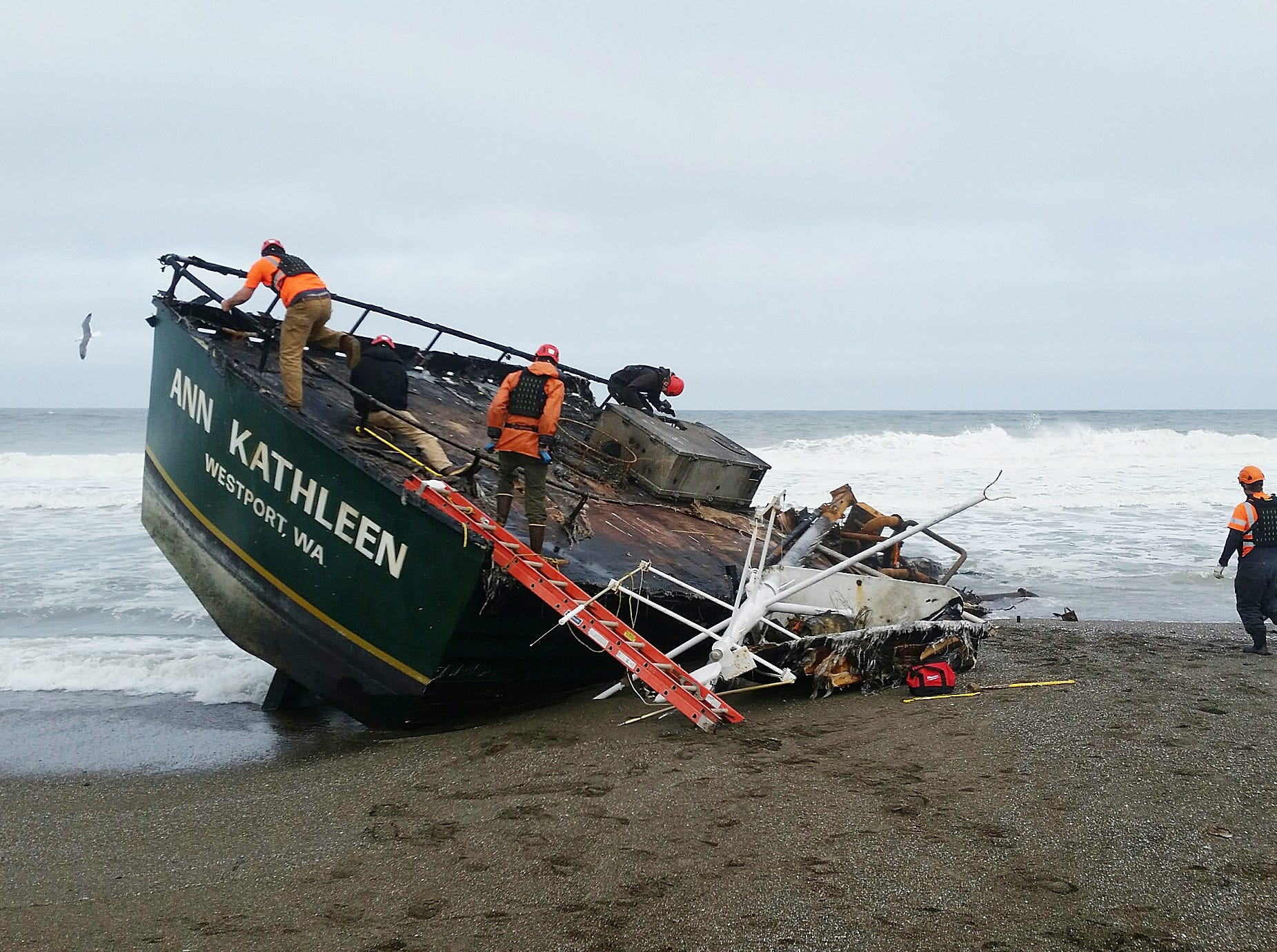 Responders examine the 64-foot commercial sailing vessel Ann Kathleen that beached near Bandon, May 4, 2019.