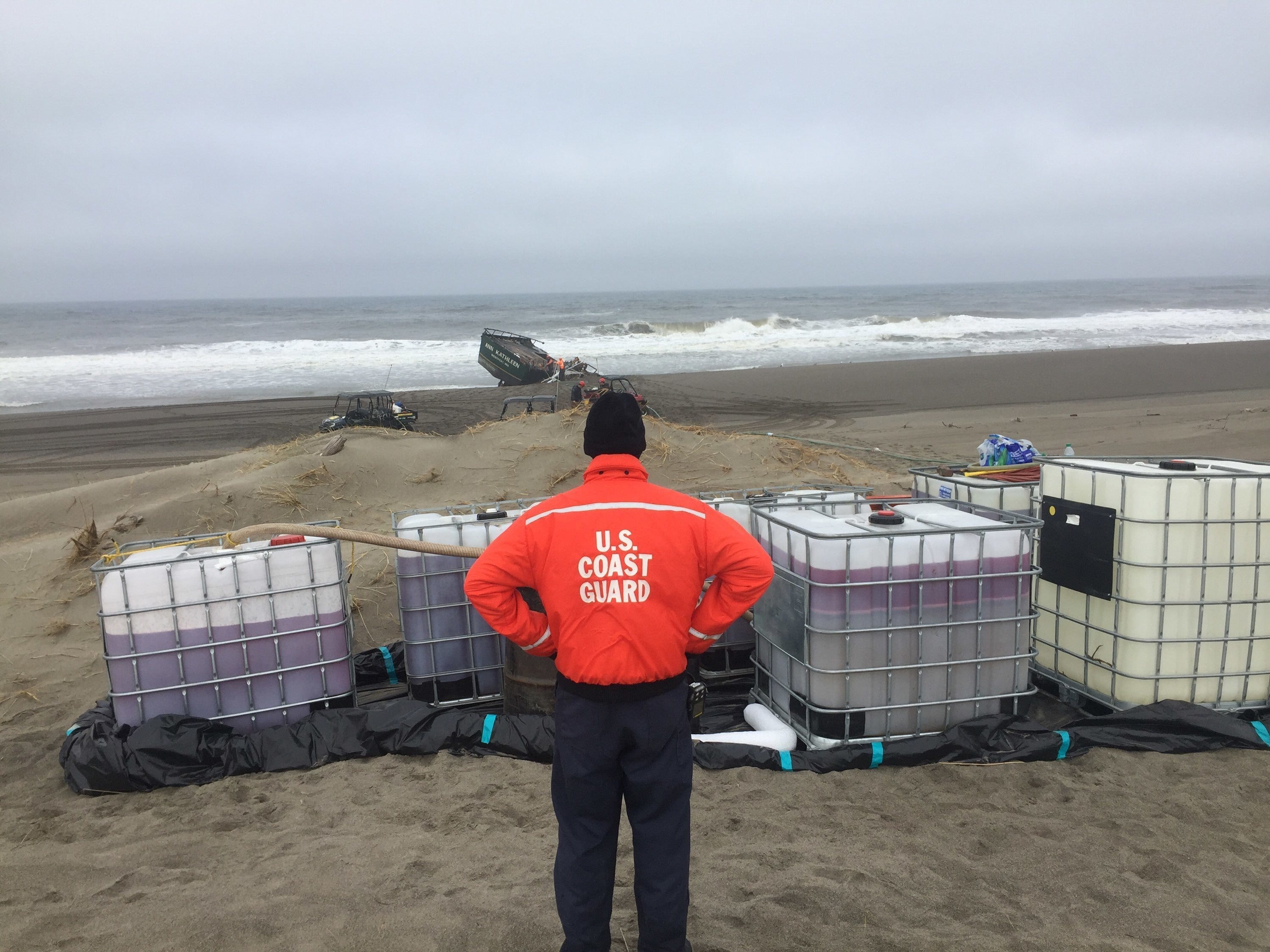 A Coast Guard member surveys six 275-gallon totes containing diesel fuel removed from the fishing vessel Ann Kathleen on a beach near Bandon, May 5, 2019.