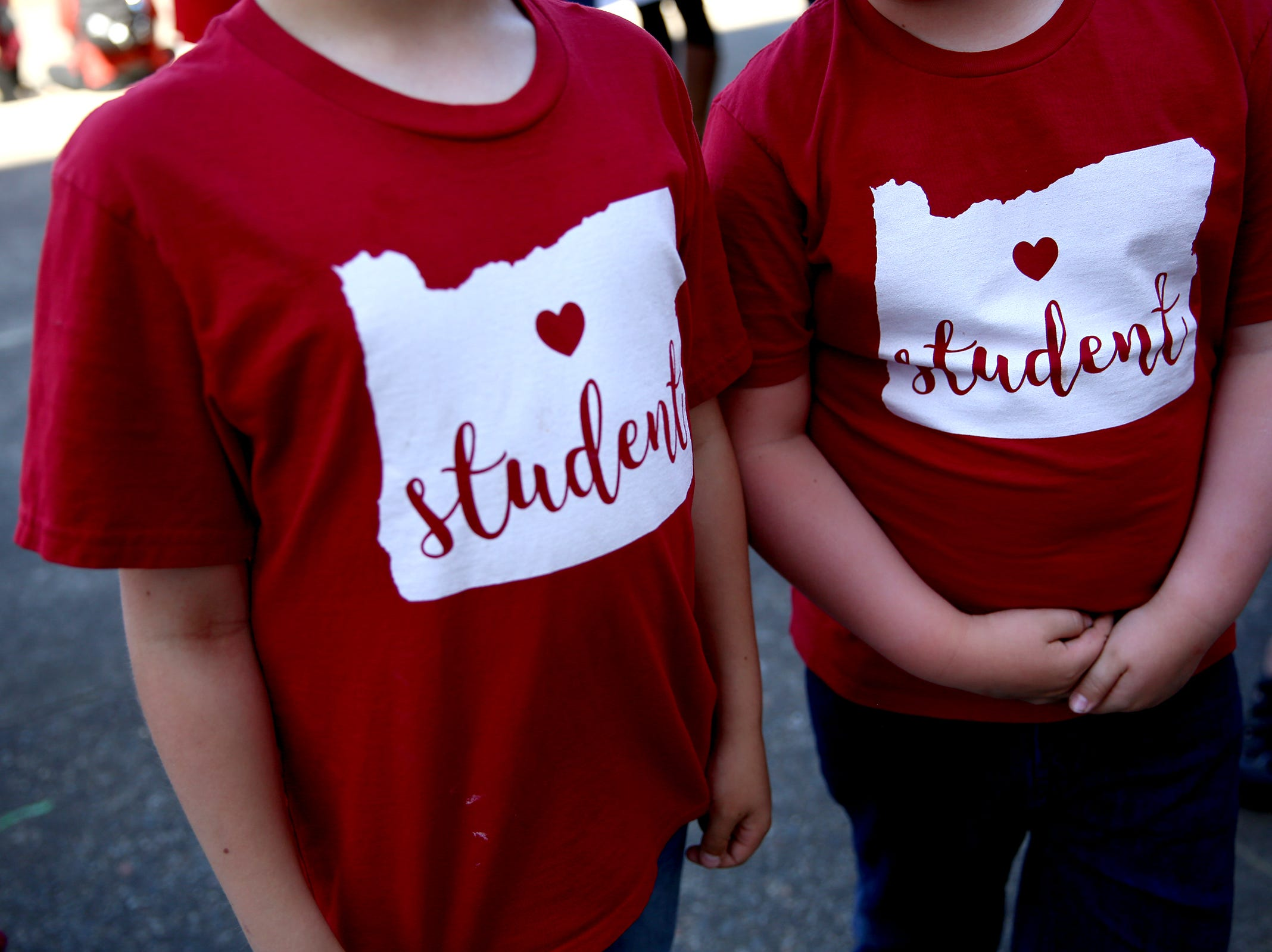 Two students wear t-shirts supporting Red for Ed during a rally for education funding where thousands of teachers and education activists marched from Riverfront Park to the Oregon State Capitol in Salem on May 8, 2019.