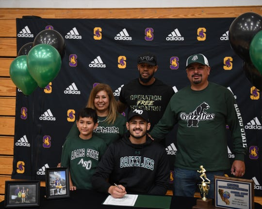 Ivan Curiel Jr. (front, center) signed his official letter of intent Wednesday to play football with the Adams State Grizzlies.