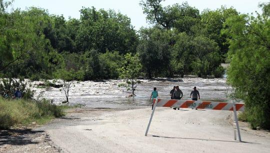 Onlookers stop to take photos of Harkey's Low Water Crossing in Mertzon, Texas, April 8, 2019.