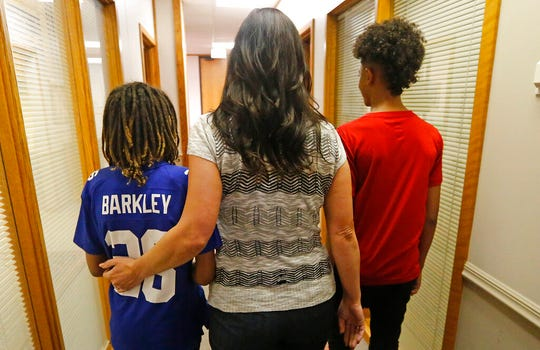 Brenda Mayes walks with her sons following a news conference Tuesday, May 7, 2019, in Salt Lake City. Mayes, sued Utah school administrators, alleging that a school bus driver trapped her older son's backpack in the door and drove away in a racially motivated event. (AP Photo/Rick Bowmer)