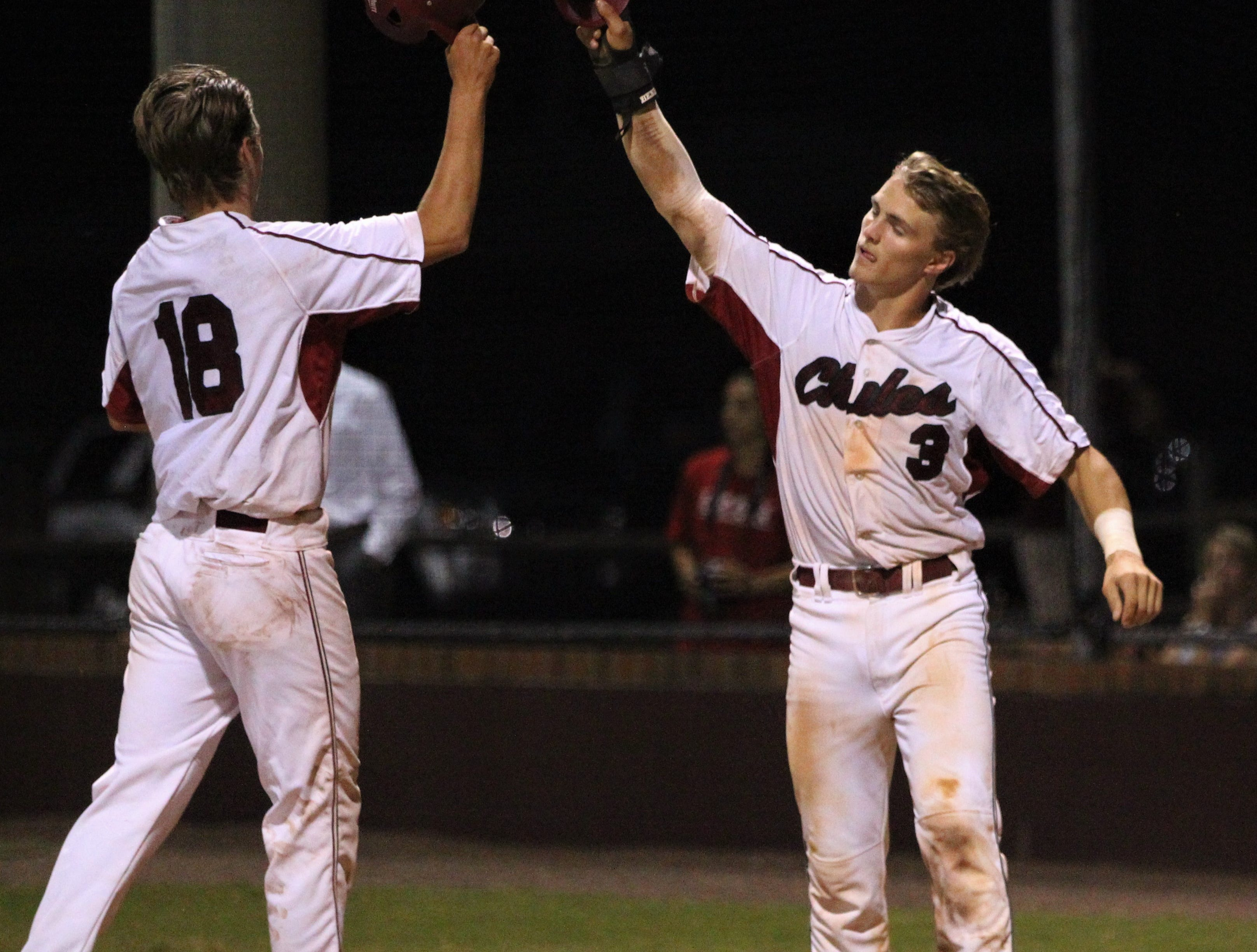 Chiles' William Kilduff (18) and Garrett Greene (3) celebrate scoring two more runs as Chiles beat Leon 10-6 during a District 2-8A semifinal on May 7, 2019.