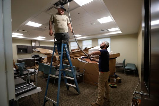 Two men work to put some of the finishing touches on the community room in the new FSU PrimaryHealth center on the southwest side of Tallahassee Wednesday, May 8, 2019.