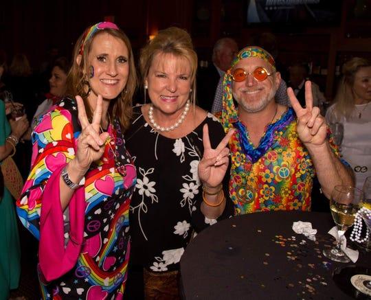 Traci Preuss, left, Barbara Sharp and Adam Preuss at the Mental Health Association's Dance Through the Decades Party.