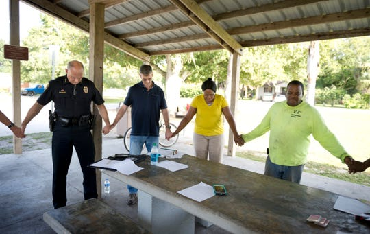 In an effort to help curb crime and put residents in touch with city officials and law enforcement, residents of the Hall, Carter and James neighborhood in Fellsmere meet monthly at Grant Park. Police Chief Keith Touchberry (left) and Fellsmere City Manager Jason Nunemaker (second from left) have been on hand at the meetings like this one on July 8, 2015, to speak with residents on a regular basis.