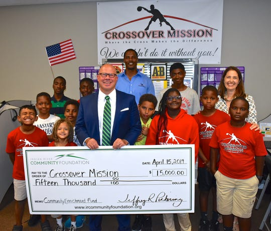 Indian River Community Foundation CEO Jeff Pickering, center, with Crossover Mission Chief of Operations Antoine Jennings and Crossover Mission Executive Director Cathy De Schouwer with Crossover Mission students and the $15,000 check from the Community Enrichment Fund.