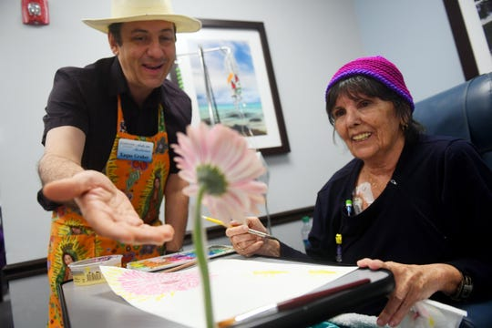 """""""I'll have to sit here for hours during my treatment and being able to do something a little active makes the time go by so much faster,"""" said Carole Crowe, a patient at Florida Cancer Specialists in Vero Beach, as she works on a watercolor painting of a flower with local artist and teacher Xaque Gruber on Wednesday, May 8, 2019, in Vero Beach. The Cultural Council of Indian River County has partnered with the cancer treatment facility to pilot an Art in Medicine Program, bringing in artists, musicians, and performers to interact with patients while they undergo treatment. """"Going through treatment can be a very stressful time,"""" said Gruber, who has experience teaching art with Alzheimer's patients and in assisted living homes. """"When you're getting treatment in one arm but creating something beautiful with the other, it can be quite comforting."""""""