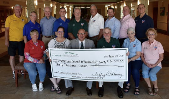 The Executive Board of the Veteran's Council of Indian River County accepts a $30,000 check from Indian River Community Foundation CEO Jeff Pickering, seated center. Pictured are, front row, from left, Kathy Allston, Kim Pilger, Pickering, Sam Kouns, Pat Geyer and Michelle Dale, with, back row, Marty Zickert, Tony Young, Andy Paul, Matthew Scheidel, Carroll Oates, Ken Dale, Dillon Roberts, Jim Romanek and Nick DeMarco.