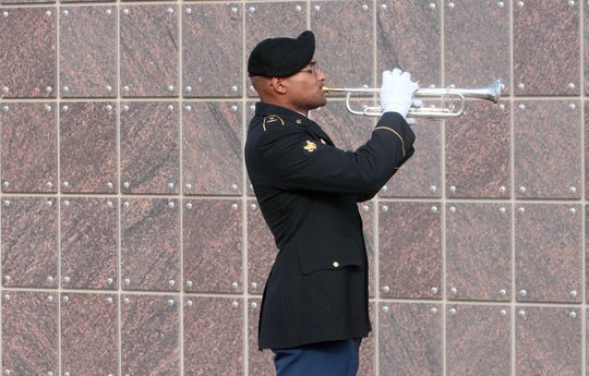 A member of the 1st Armored Division Band plays taps during a Wreaths Across America dedication ceremony at Fort Bliss National Cemetery.