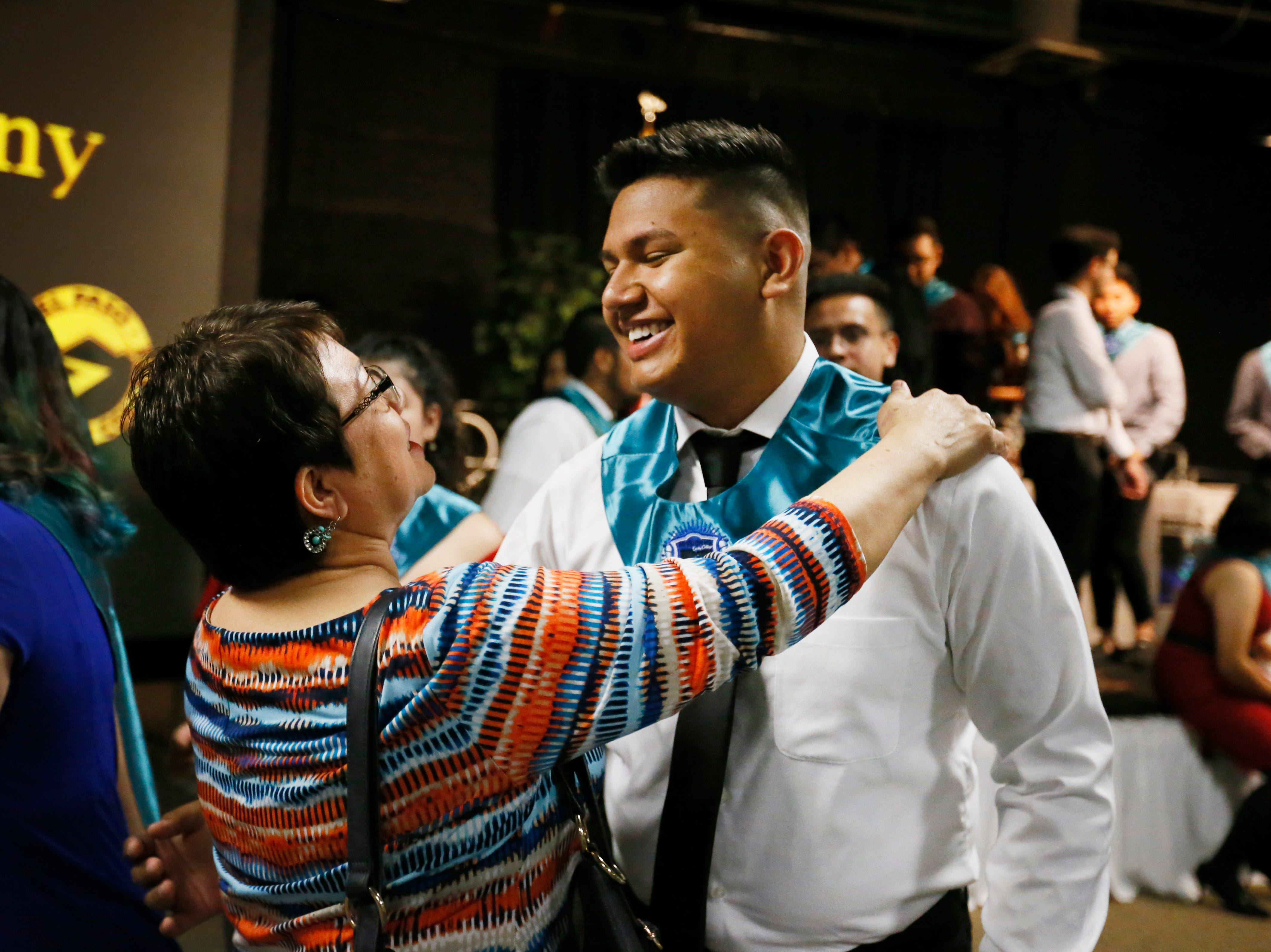 Mission Early College High School Spanish teacher Magdalena Contreras gives her former student Claudio Johnston a hug after their stoling ceremony Tuesday, May 7, at EPCC Administrative Service Center in El Paso.