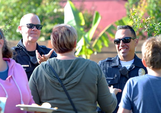 Ventura Police Department Sgt. Trenner Marchetti (left) and Cpl. Anthony Morales talk with local residents during a Tacos with the Cops fundraising event at the Restore Ventura Garden in Ventura on May 3. Sales of tacos benefitted three local youth programs: Kids Garden Brigade, Creative Play and Avenida Surf Club.