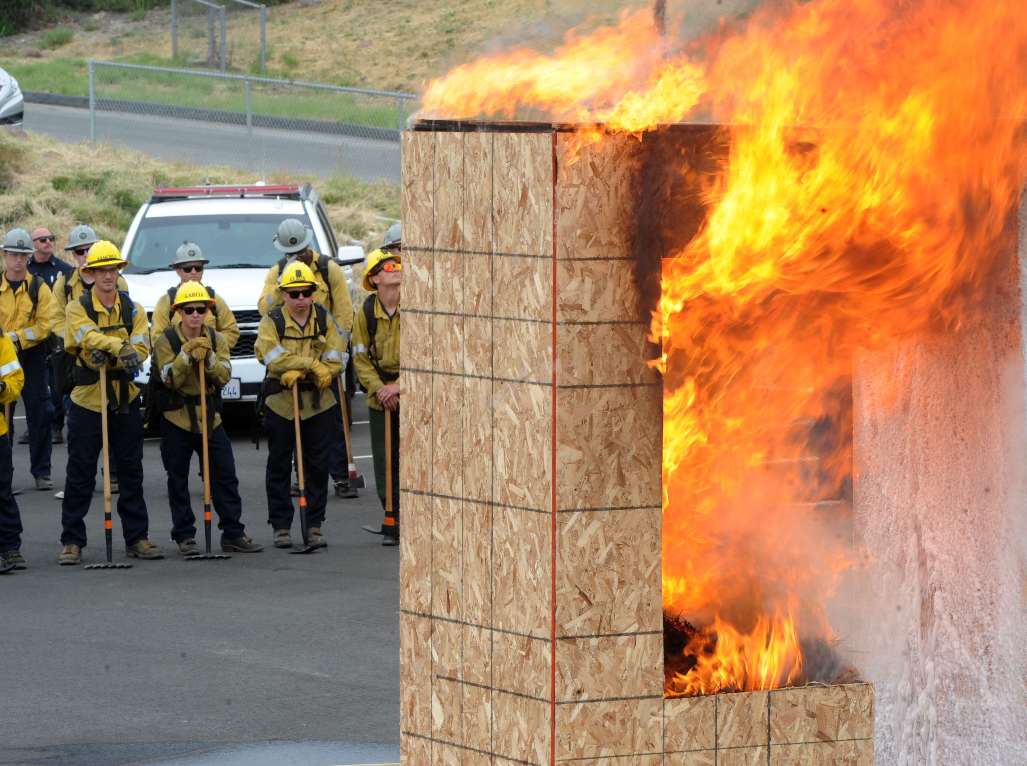 """Firefighters watch a fire demonstration Wednesday during the Southern California """"Ready for Wildfires"""" event at the Reagan Library in Simi Valley on Wednesday. The Ventura County Fire Department presented the event in partnership with Cal Fire. In addition to helicopter drops and fire demonstrations, about 400 goats were set loose to eat brush on the hills of the library."""