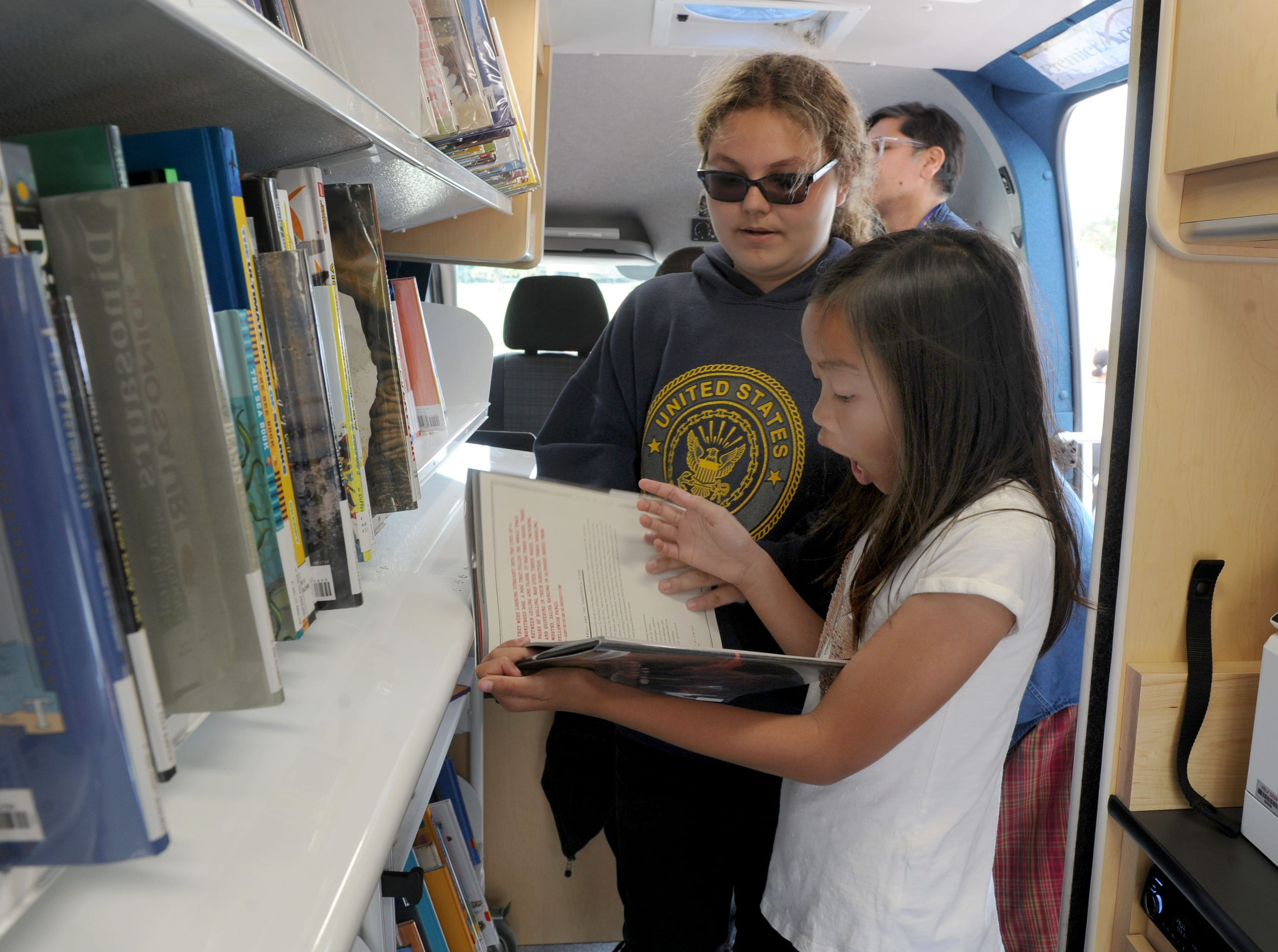 Mhyca Chua, front,  is surprised to find a Harry Potter book with her friend Jaylee Kiel inside the Ventura County library system's new mobile library Tuesday at the Ventura County Government Center. The 26-foot, fuel-efficient vehicle is stocked with many of the same services found in a traditional library.
