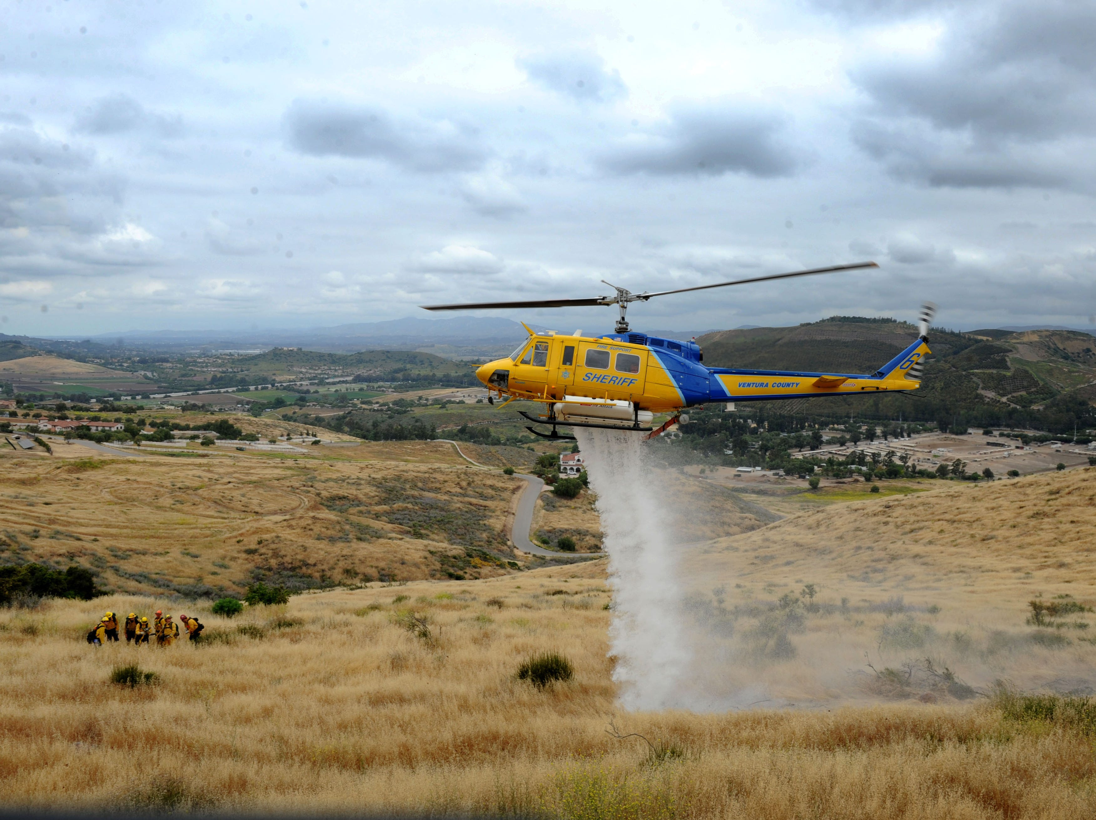 """A Ventura County Sheriff's Office helicopter demonstrates a water drop Wednesday at the Southern California """"Ready for Wildfires"""" event at the Reagan Library in Simi Valley."""