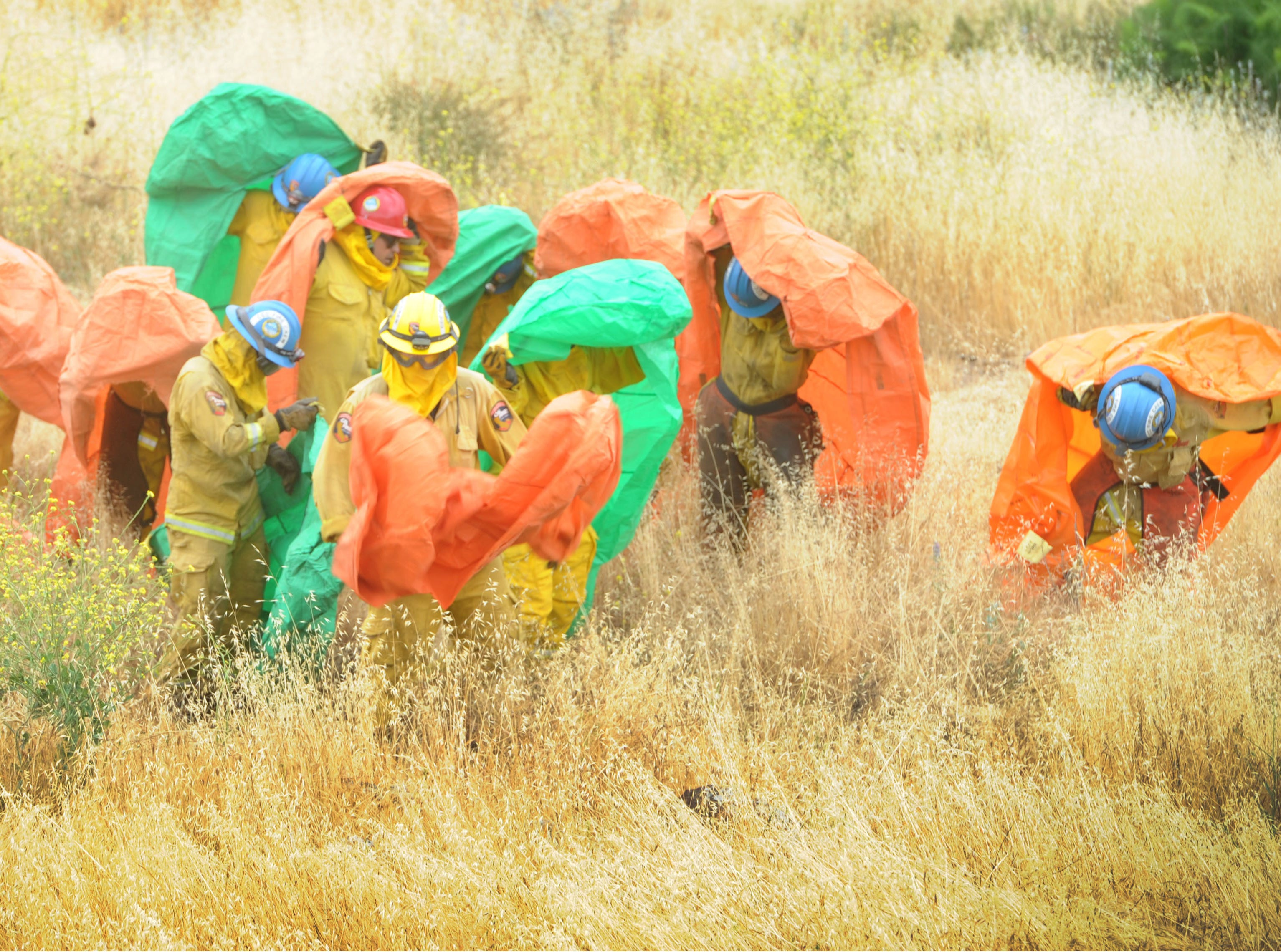 """Hand crews demonstrate how to get into fire shelters Wednesday at the Southern California """"Ready for Wildfires"""" event at the Reagan Library in Simi Valley."""