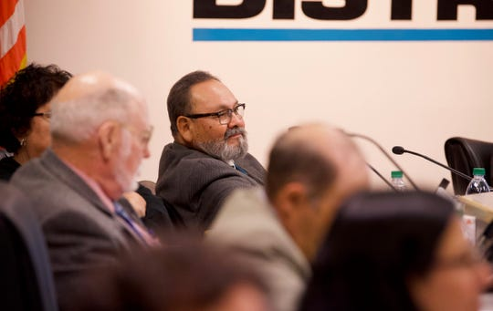 Visalia school board Trustee Juan Guerrero listens and smirks as supporters of Todd Oto speak out Tuesday.
