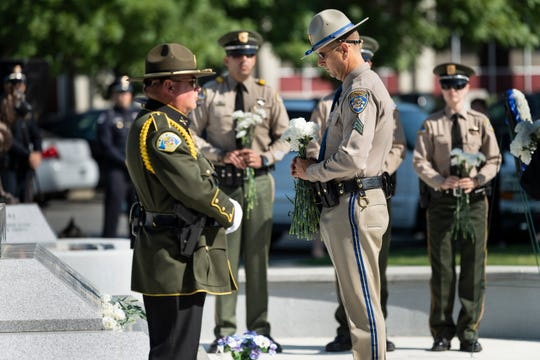 Officers place carnations for fallen officers during the Tulare County Peace Officer Memorial Ceremony on Wednesday, May 8, 2019.