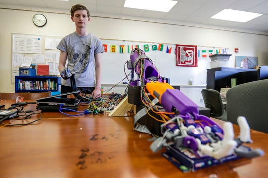Student Connor Deffner demonstrates on Wednesday, April 24, 2019, how to control the robotic hand he created at Wausau Engineering and Global Leadership Academy charter high school in Wausau, Wis.