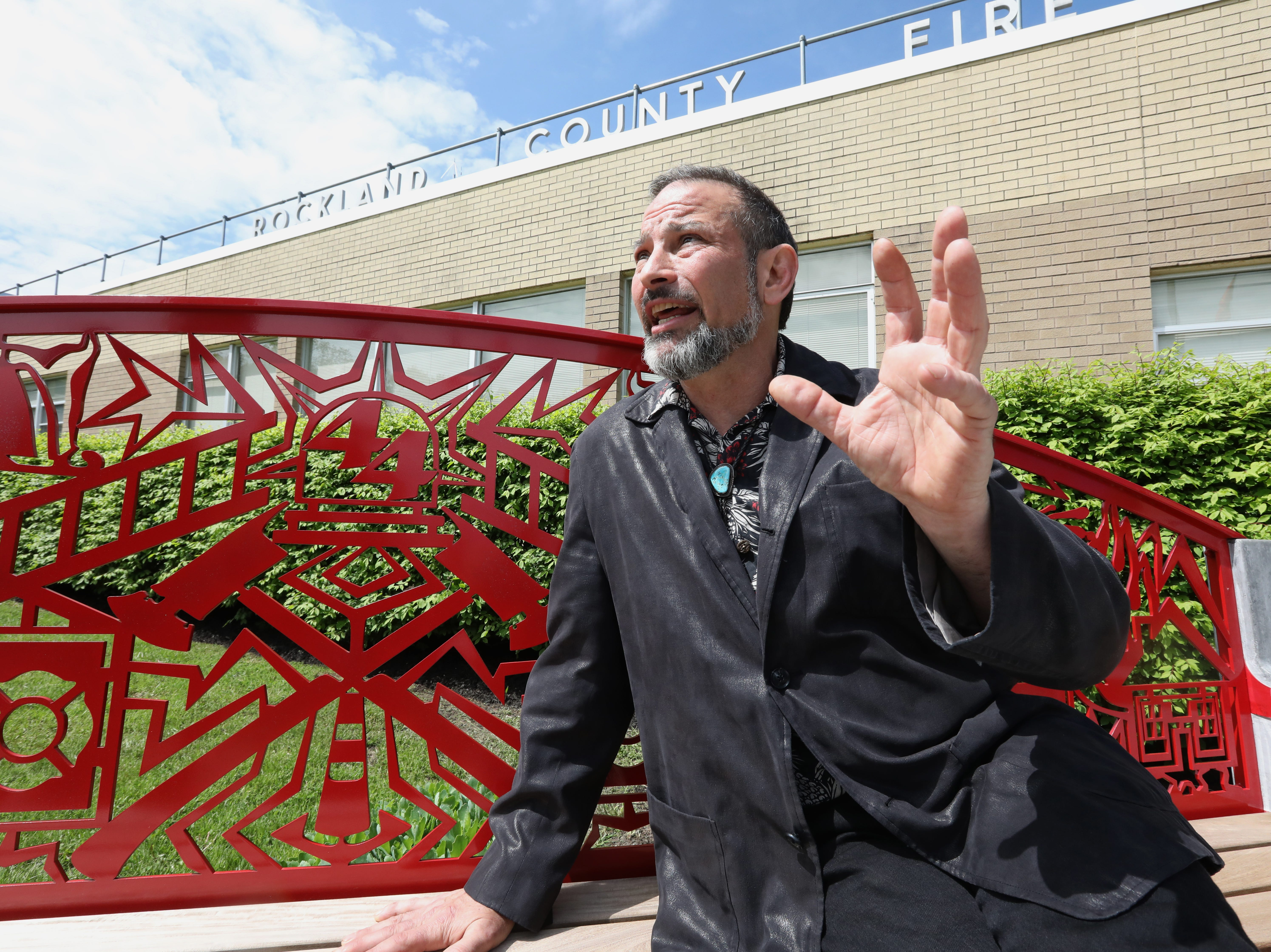 Sculptor Eric David Laxman on one of the two benches he created at the Rockland County Fire Training Center in Pomona May 8, 2019. The benches that honor Rockland's firefighters and emergency responders, were funded by the Rockland County Art in Public Places Committee.