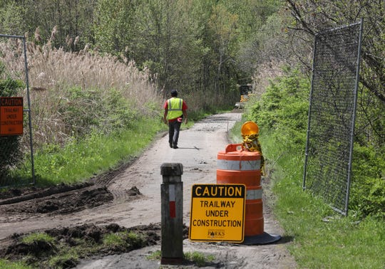A trailway under construction sign is pictured as excavators work at the site of the north county trailway in Millwood, as they repair and rebuild the popular site for cyclists, joggers and walkers, May 8, 2019.