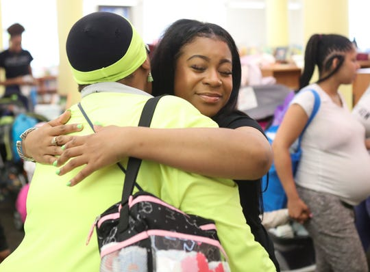 Giovanna Andrews hugs a visitor during the Thousand Bib and Book Giveaway at the Wilmington Public Library. Andrews leads Harper's Heart, an organization that helps expectant or new mothers.