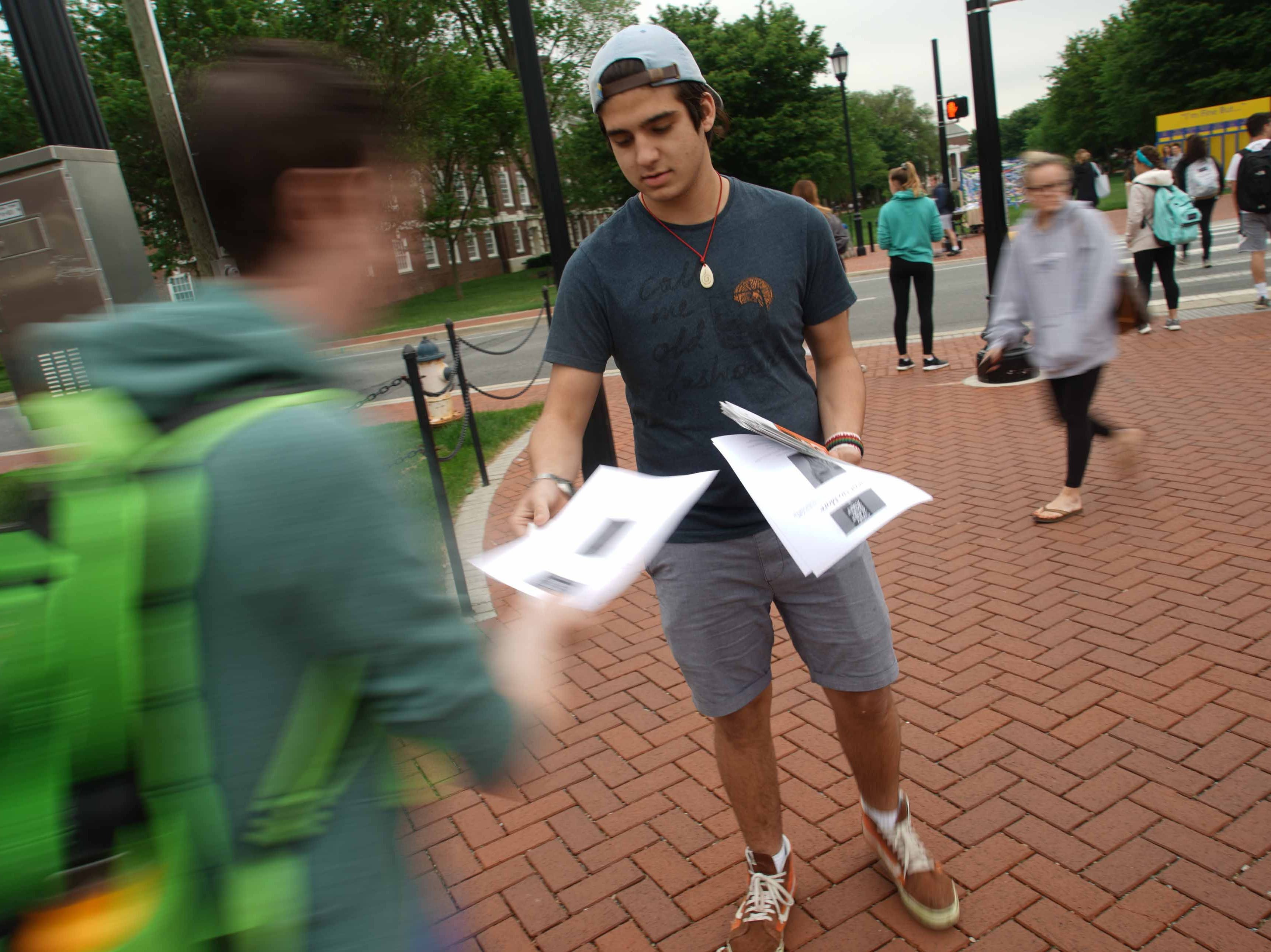 Jeremy Reissman, 18, a freshman, hands out information on what to do if you've sexually assaulted during a silent protest on the university's Green Wednesday afternoon.