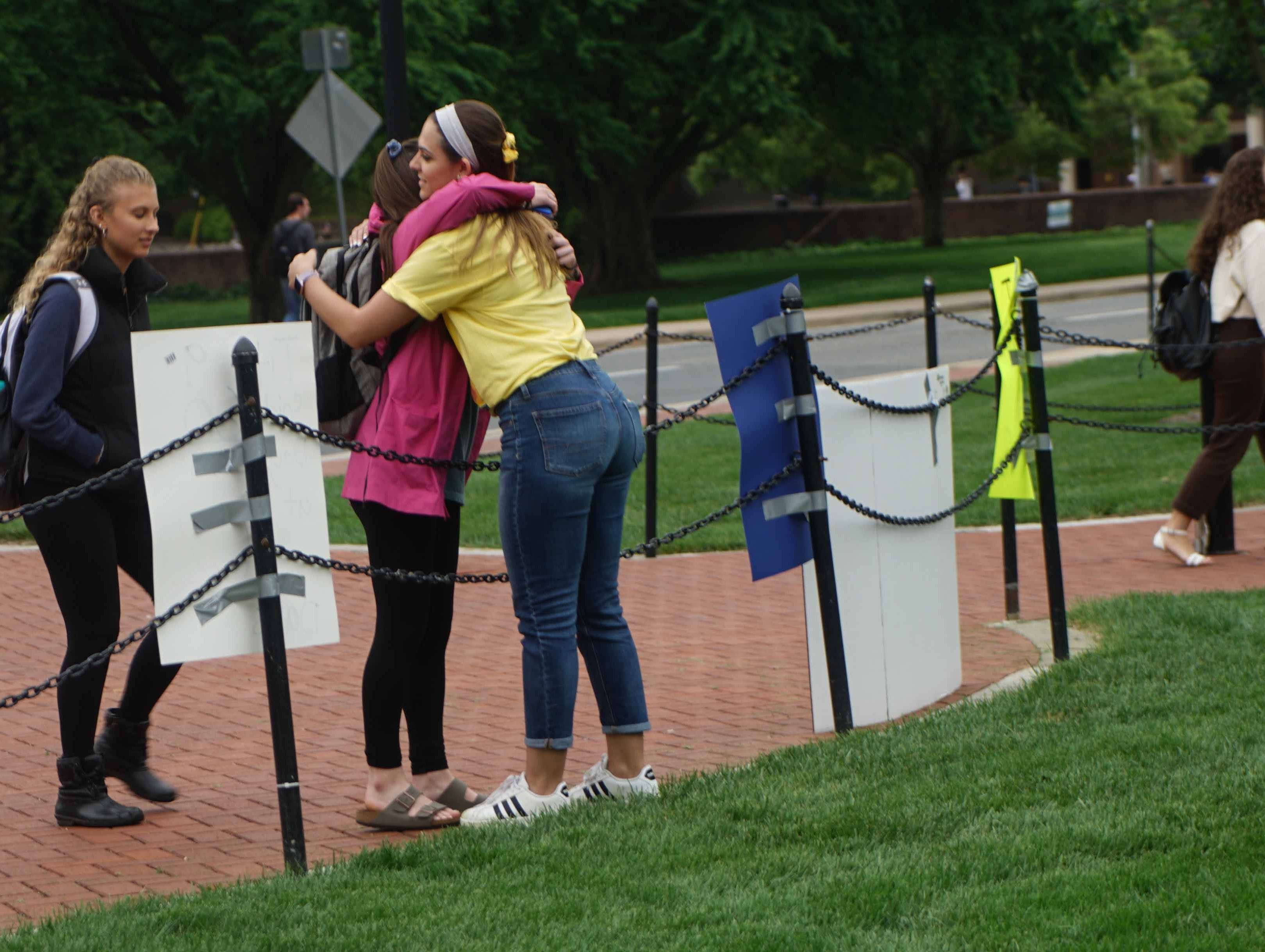 Alyvia Pauzer, 19, a sophomore at the University of Delaware, gets a hug from supporters passing by a silent protest that she held on the  university's Green Wednesday afternoon to bring attention to state prosecutors decision not to file charges in her sexual assault case.
