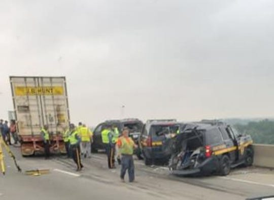 Two state troopers were hurt early Wednesday morning when a tractor-trailer struck one of their vehicles, causing a chain reaction that sent both to the hospital, police said.