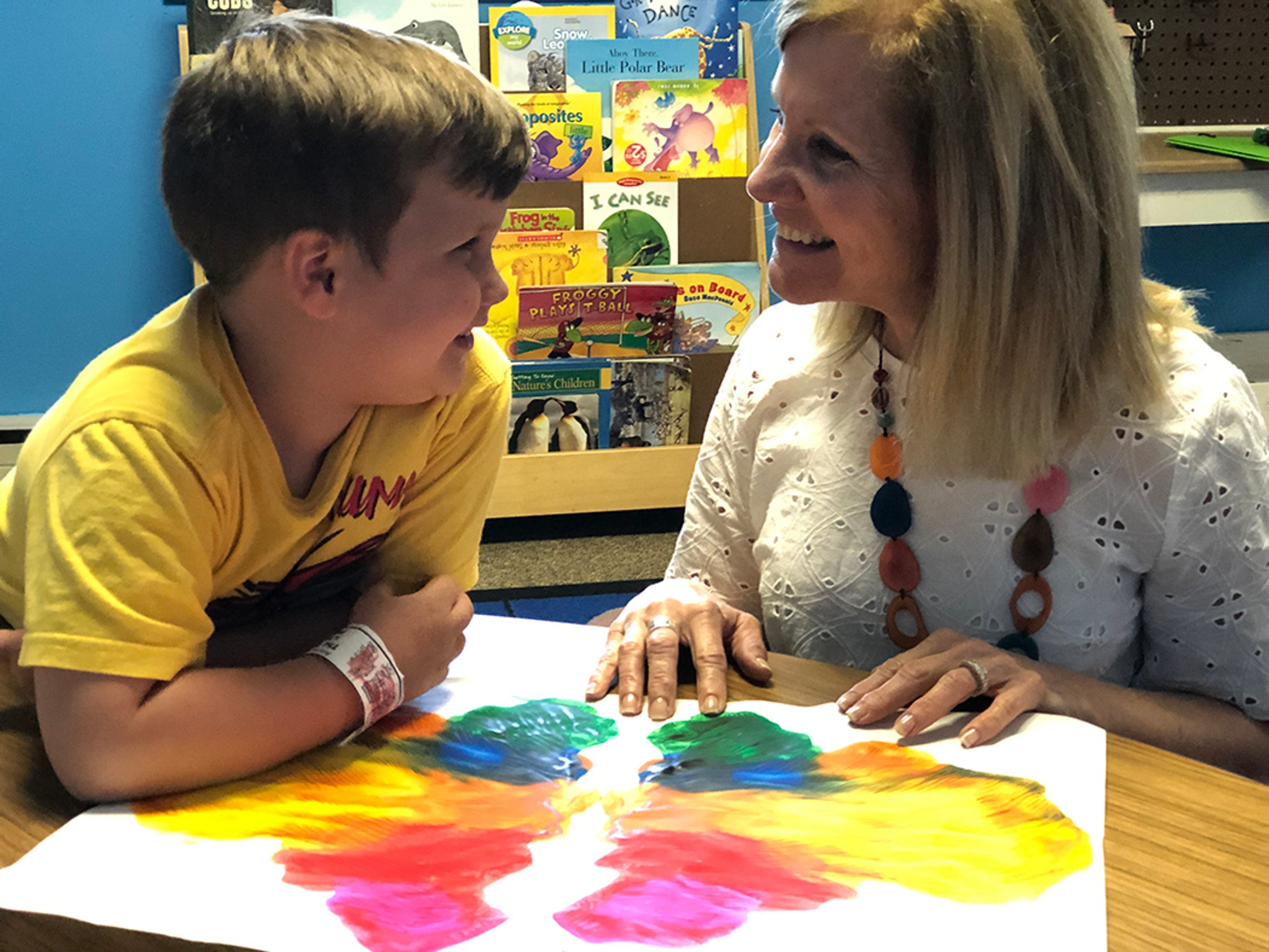 North Terrace Preschool student, Grady, shows Colleen Romito his butterfly because he knows Miss Colleen likes them.