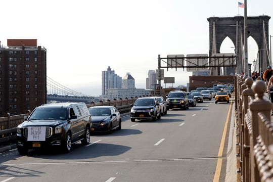 Uber and Lyft drivers, with signs on their vehicles supporting better wages, cross the Brooklyn Bridge in a caravan of about 25 vehicles, Wednesday, May 8, 2019 in New York. The protests arrive just ahead of Uber's initial public stock offering, which is planned for Friday. (AP Photo/Mark Lennihan) ORG XMIT: NYML101