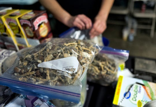 A vendor bags psilocybin mushrooms at a pop-up cannabis market in Los Angeles on Monday, May 6, 2019.