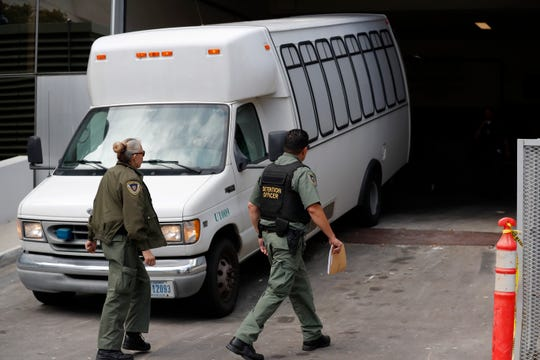 In this Tuesday, March 19, 2019 file photo, a van carrying asylum seekers from the border is escorted by security personnel as it arrives at immigration court, in San Diego. A federal appeals court ruled Tuesday, May 7, 2019, that the Trump administration can force asylum seekers to wait in Mexico for immigration court hearings while the policy is challenged in court, handing the president a major victory, even if it proves temporary.