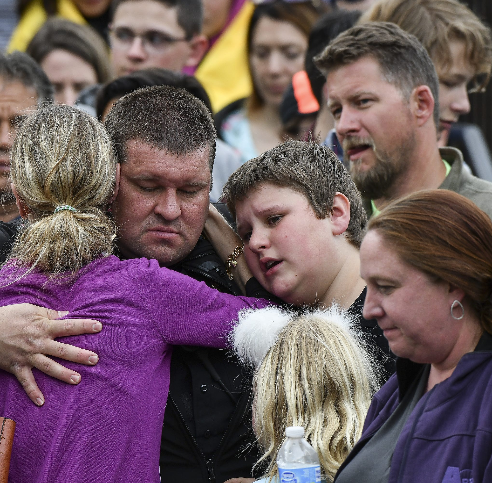 A police officer hugs his family after they were evacuated to the Northridge Recreation Center after a shooting at STEM School Highlands Ranch.