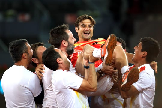 David Ferrer is lifted on the court by his family and friends at the Mutua Madrid Open.