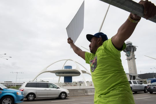 Uber driver Jason Garcia, 51, pickets at Los Angeles International Airport. Uber and Lyft drivers in some cities across the country turned off their apps to strike for higher wages and benefits