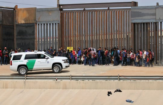 Central American migrants are detained by U.S. Border Patrol agents at the border wall near Ciudad Juarez, Mexico, on May 7, 2019.