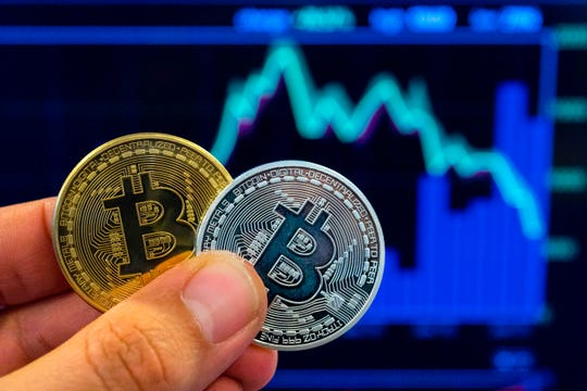 """A picture taken on February 6, 2018 shows a person holding a visual representation of the digital crypto-currency Bitcoin, at the """"Bitcoin Change"""" shop in the Israeli city of Tel Aviv."""