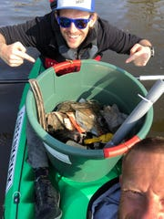 A volunteer shows off the trash he collected through GreenKayak.