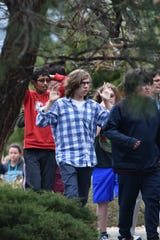 Students and teachers raise their arms as they exit the scene of a shooting at the STEM School Highlands Ranch.