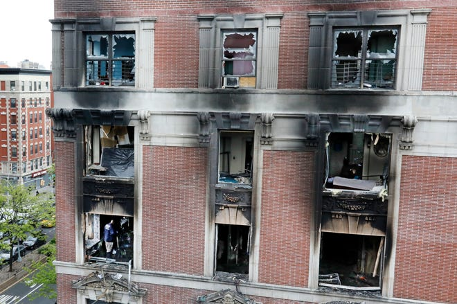 Fire marshals sift through a burned out apartment in New York's Harlem neighborhood, on May 8, 2019. Six people, including four children, were killed Wednesday when an overnight fire ravaged an apartment in a city-owned Harlem building.